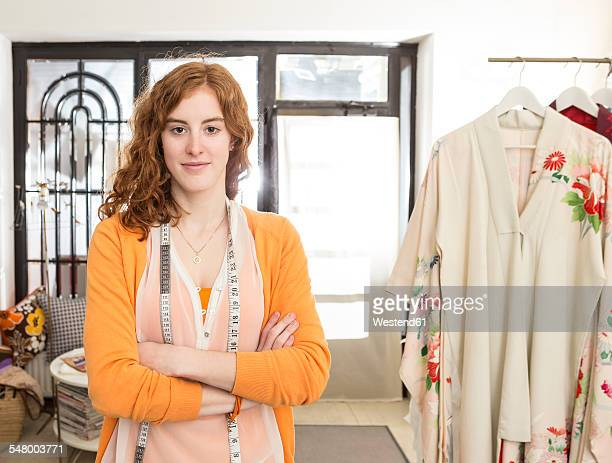 Portrait of smiling female fashion designer with tape measure at her studio