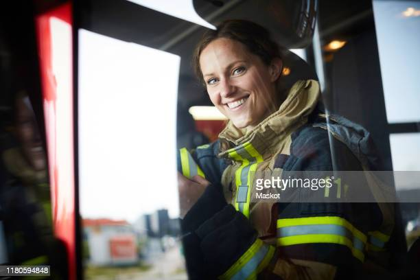portrait of smiling female firefighter sitting in fire engine - firefighter stock pictures, royalty-free photos & images