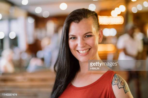 portrait of smiling female hipster at restaurant - half shaved hairstyle stock pictures, royalty-free photos & images