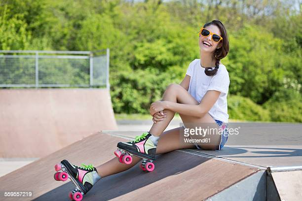 Portrait of smiling female inline-skater with sunglasses