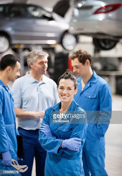 portrait of smiling female mechanic with co-workers in auto repair shop - repair shop stock pictures, royalty-free photos & images