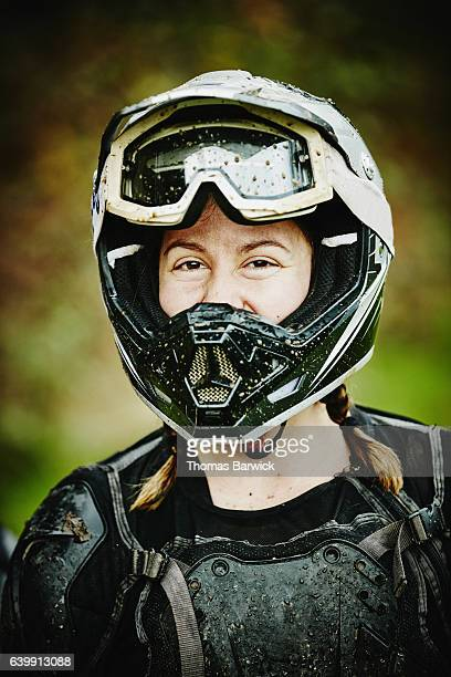 Portrait of smiling female motorcyclist after riding dirt bike