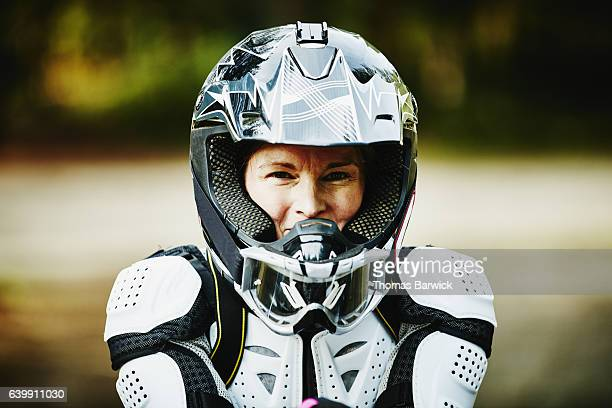 Portrait of smiling female motorcyclist in helmet and pads