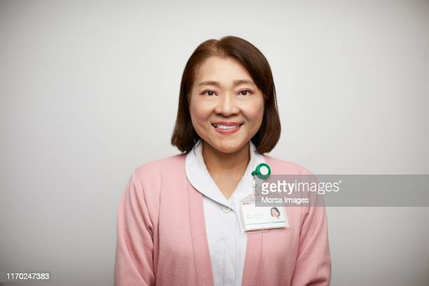 portrait of smiling female nurse in uniform - identity card stock pictures, royalty-free photos & images