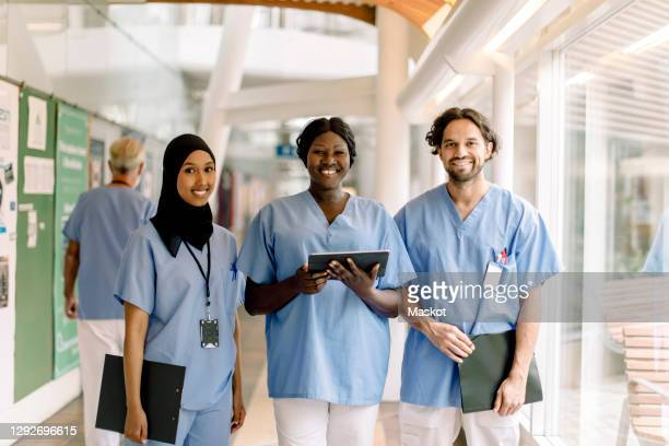 portrait of smiling female nurse with digital tablet by colleagues in hospital - religious dress stock pictures, royalty-free photos & images