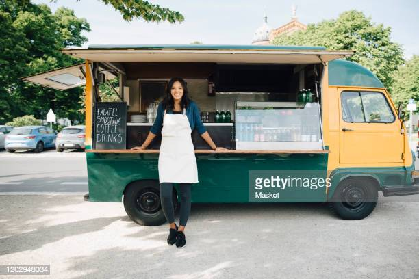 portrait of smiling female owner standing against food truck - food truck stock pictures, royalty-free photos & images