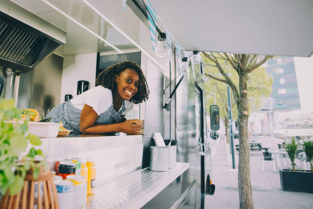portrait of smiling female owner standing in food truck picture