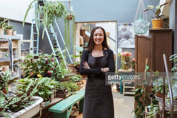 portrait of smiling female owner standing with arms crossed by potted plants at store - florist stock pictures, royalty-free photos & images