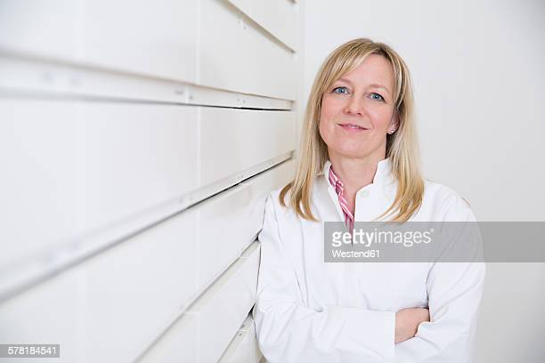 Portrait of smiling female pharmacist leaning on drawer cabinet