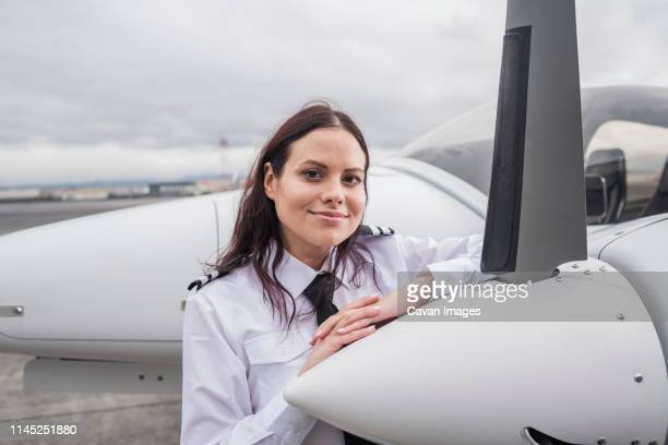 portrait of smiling female pilot standing by airplane on airport runway against cloudy sky - piloting stock pictures, royalty-free photos & images