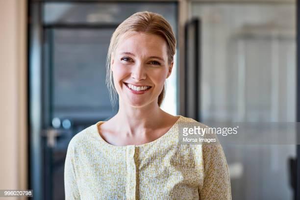 portrait of smiling female professional at office - informeel zakelijk stockfoto's en -beelden