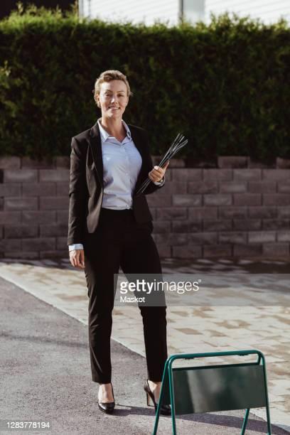 portrait of smiling female real estate agent standing at sidewalk - une seule femme d'âge mûr photos et images de collection