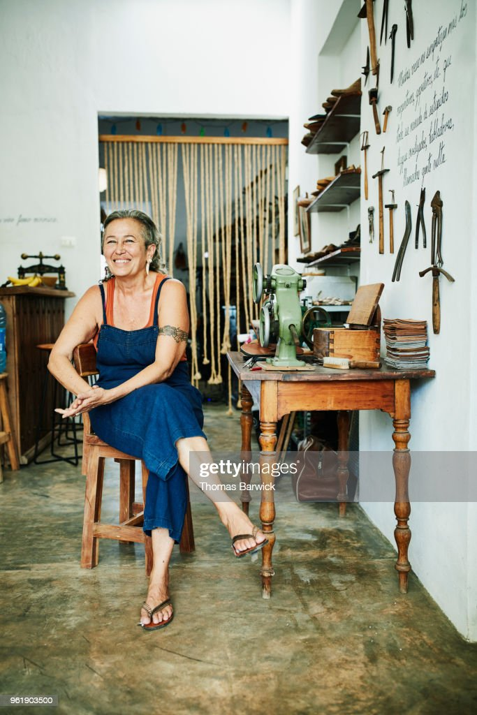 Portrait of smiling female shoemaker sitting at worktable in workshop : Stock Photo