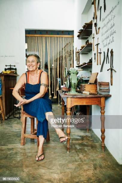 Portrait of smiling female shoemaker sitting at worktable in workshop