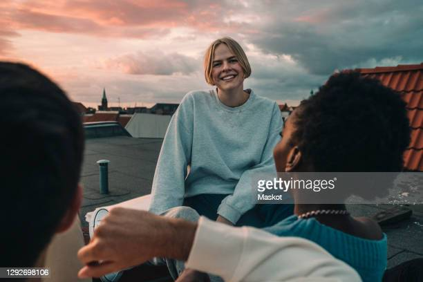 portrait of smiling female sitting with friends on building terrace during sunset - lebensstil stock-fotos und bilder