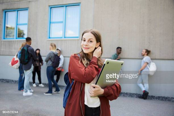 portrait of smiling female student carrying laptop while standing at university campus with friends in background - 18 19 years stock pictures, royalty-free photos & images