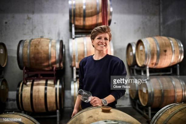 portrait of smiling female vintner in wine cellar - ワインセラー ストックフォトと画像