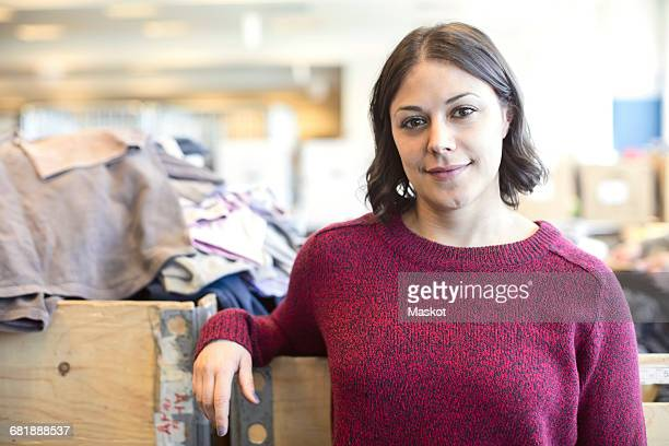 Portrait of smiling female volunteer standing against heap of clothes at workshop