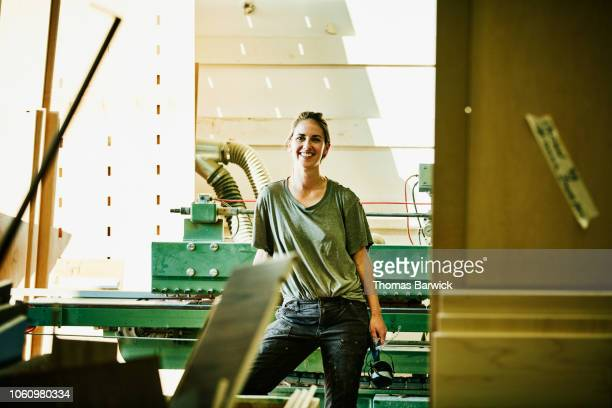 portrait of smiling female woodworker in cabinet shop - khaki green stock pictures, royalty-free photos & images