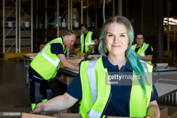 Portrait of smiling female worker with dyed hair standing against coworkers in distribution warehouse