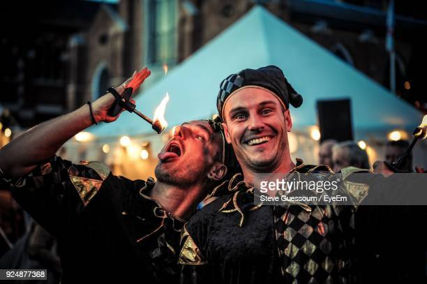 portrait of smiling fire-eater in costume with friend - performer stock pictures, royalty-free photos & images