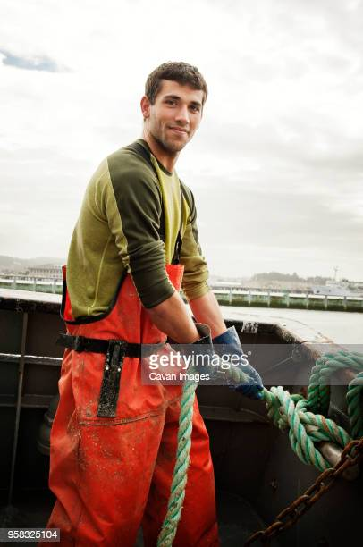 portrait of smiling fisherman pulling rope on fishing boat against sky - fisherman stock pictures, royalty-free photos & images