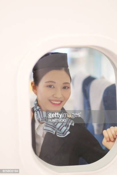 Portrait of smiling flight attendant in airplane