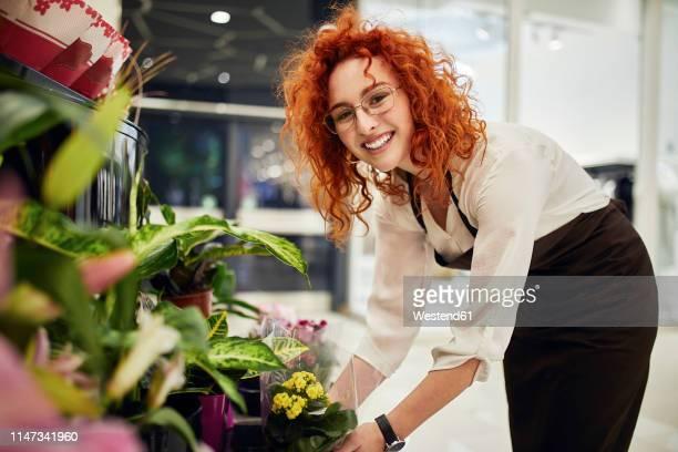 portrait of smiling florist arranging flowers in flower shop - florist stock pictures, royalty-free photos & images
