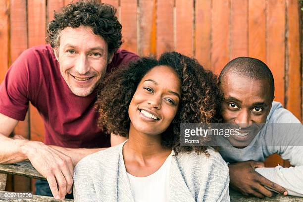 Portrait of smiling friends against wooden fence