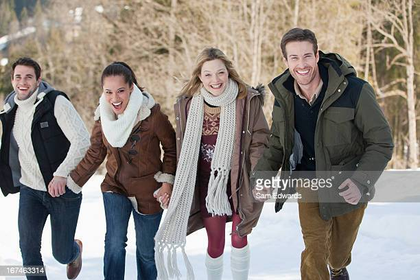 Portrait of smiling friends holding hands and running in snow