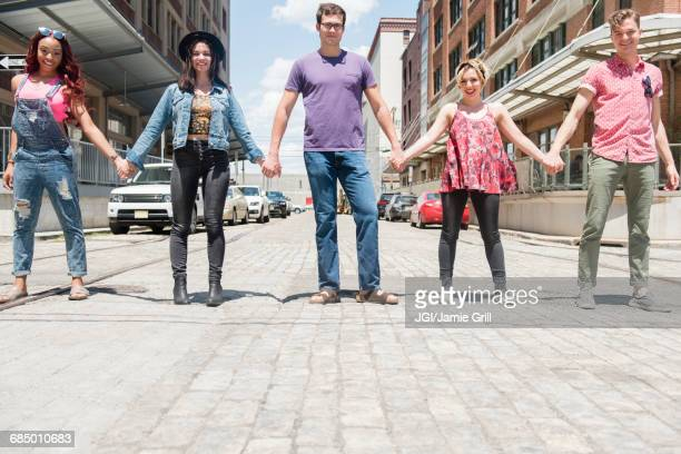Portrait of smiling friends holding hands in city street
