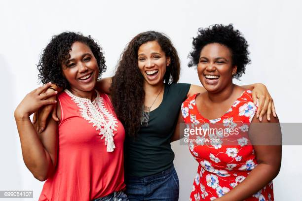 portrait of smiling friends hugging - diverse women ストックフォトと画像