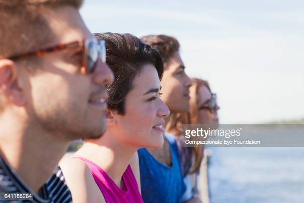 Portrait of smiling friends looking out across river