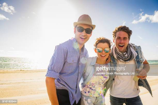 Portrait of smiling friends on sunny beach