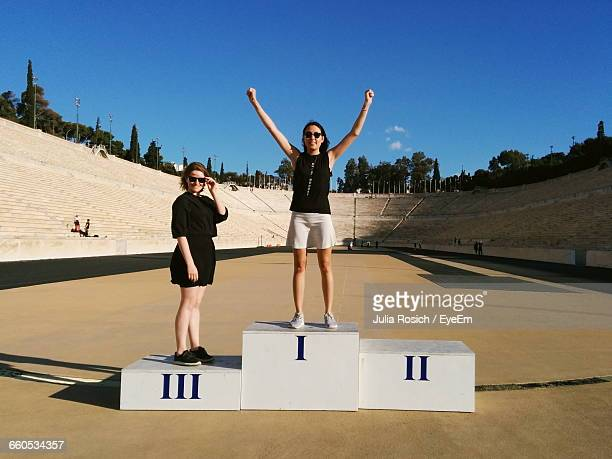 portrait of smiling friends on winners podium at panathinaiko stadium - winners podium stock pictures, royalty-free photos & images