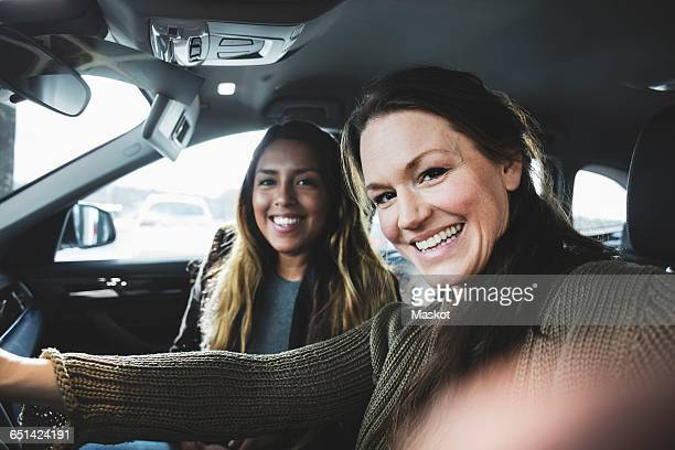 Portrait of smiling friends sitting in car at showroom