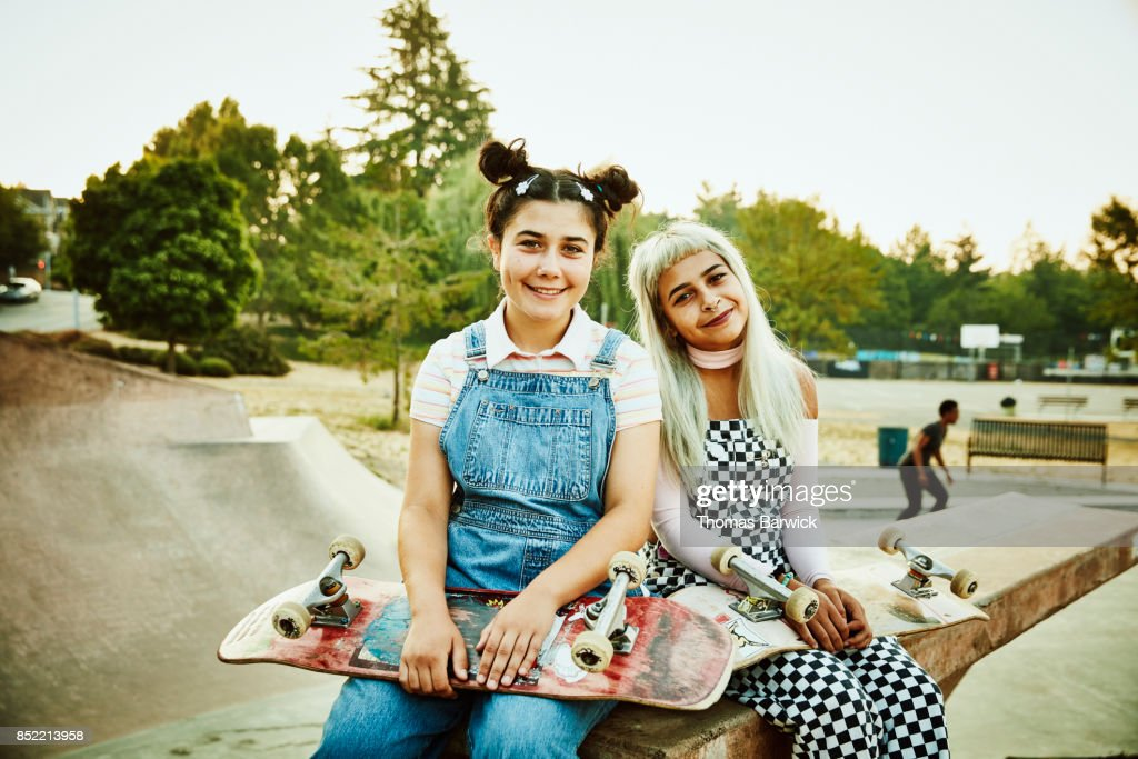 Portrait of smiling friends sitting on ramp in skate park on summer morning : Stock Photo