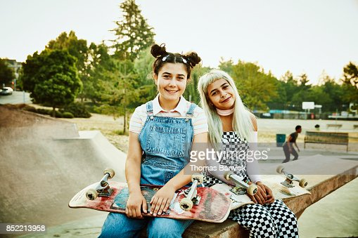 Portrait of smiling friends sitting on ramp in skate park on summer morning