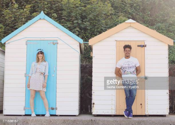 Portrait Of Smiling Friends Standing Against Beach Hut