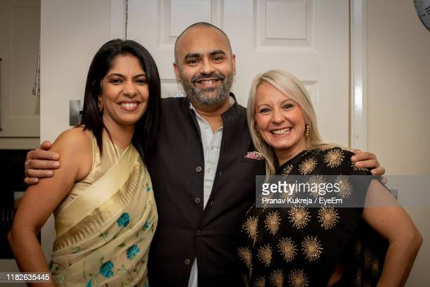 portrait of smiling friends standing against door - leicester stock pictures, royalty-free photos & images