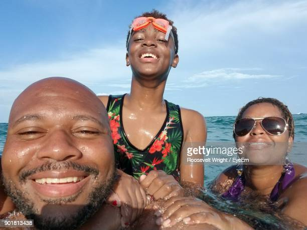Portrait Of Smiling Friends Swimming In Sea Against Sky