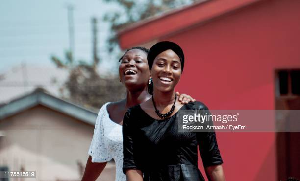 portrait of smiling friends with arm around in city - ghana stock pictures, royalty-free photos & images