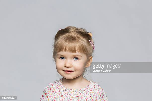 Portrait of smiling girl against gray background