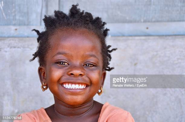 portrait of smiling girl against wall - ghana africa fotografías e imágenes de stock