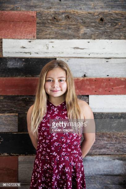 Portrait of smiling girl against wooden wall