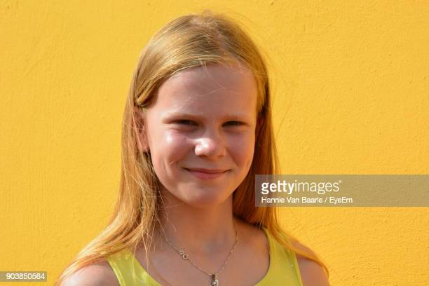 Portrait Of Smiling Girl Against Yellow Wall