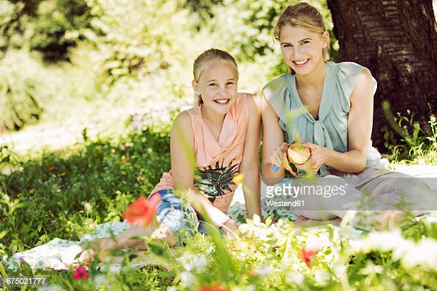 Portrait of smiling girl and young woman sitting together on blanket in a park