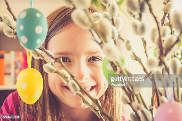 Portrait of smiling girl behind Easter bouquet