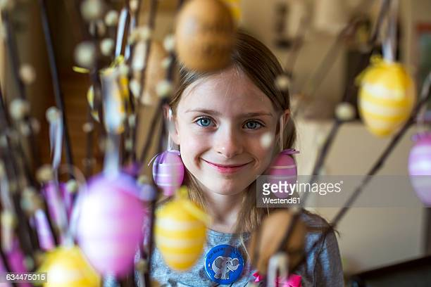 Portrait of smiling girl behind twigs of pussy willows decorated with Easter eggs