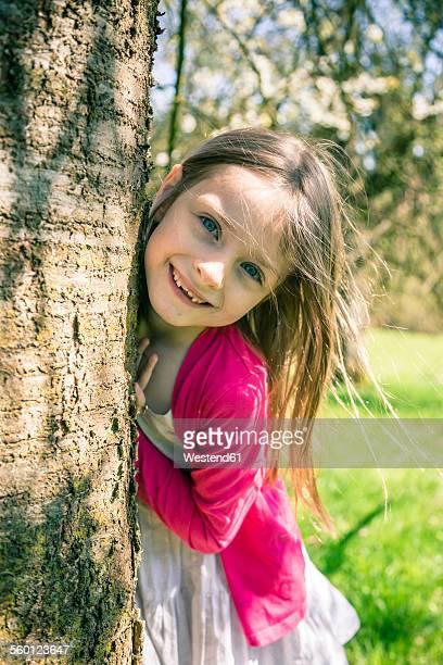 portrait of smiling girl besides tree trunk - mädchen stock-fotos und bilder